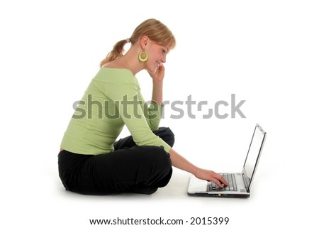 Young woman talking on a mobile phone, using a laptop - stock photo