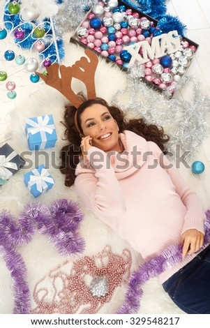 Young woman talking on mobilephone, lying on floor at xmas, wearing reindeer antler, smiling happy. - stock photo