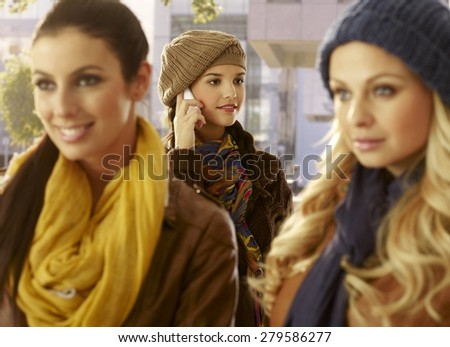 Young woman talking on mobilephone outdoors, friends waiting for her. - stock photo