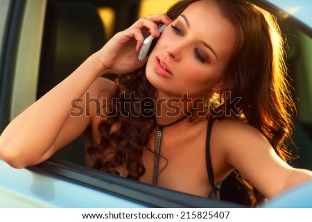 Young woman talking on phone in car. - stock photo