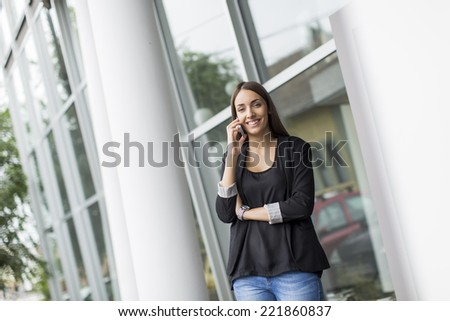 Young woman talking on the phone in front of office - stock photo