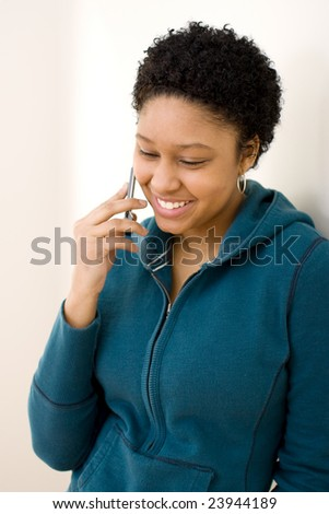 Young woman talking on the phone looking pleased. - stock photo