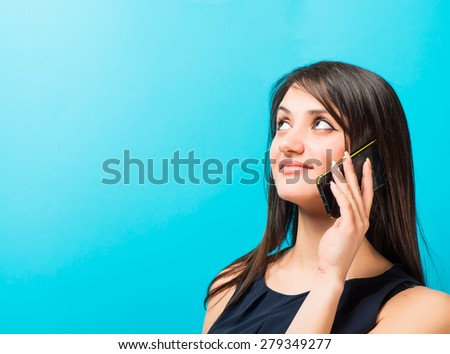 young woman talking on the phone on a blue background - stock photo