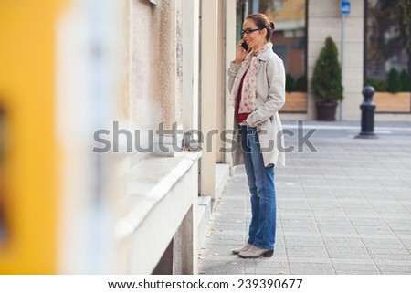 Young woman talking on the phone standing in front of the store window - stock photo