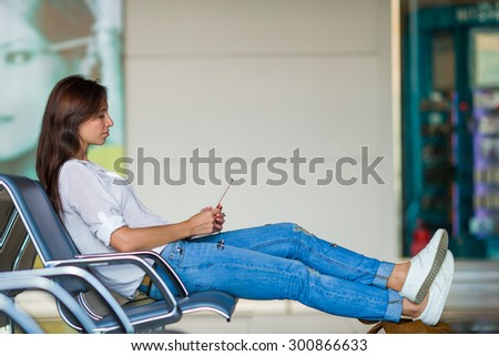 Young woman talking on the phone while waiting boarding - stock photo