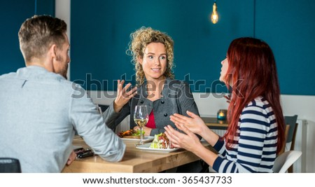Young woman talking to friends while having food at restaurant table - stock photo