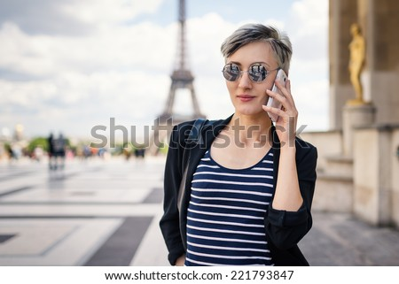 Young woman talking with mobile phone in front of the Eiffel Tower. Paris, France. Filtered image. - stock photo