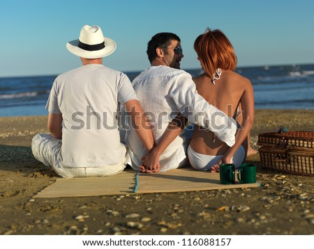 young woman talking with the boyfriend, while holding hands with another man, at a picnic by the sea shore - stock photo