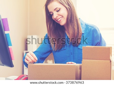 Young woman taping boxes to be shipped in her home office - stock photo