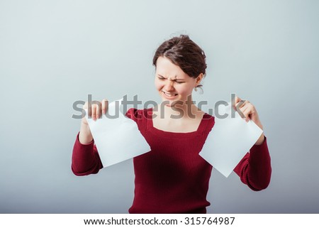young woman tears the paper - stock photo
