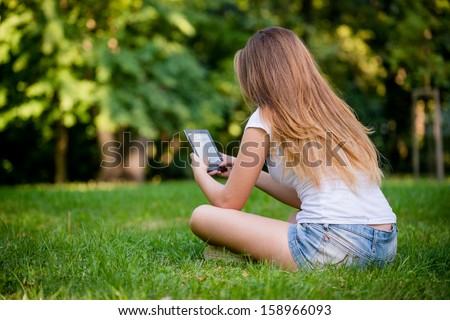 Young woman (teen girl) reading book on electronic book reader - outdoor, rear view - stock photo
