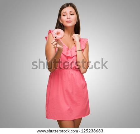 Young Woman Tempted To Eat A Donut against a grey background - stock photo
