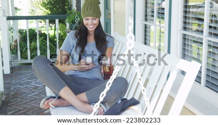 Young woman texting and sitting on porch - stock photo