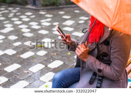Young woman texting sms in beautiful autumn park - stock photo