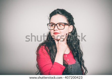 young woman thinks is a great idea, dressed in a overalls, close-up isolated on a gray background - stock photo
