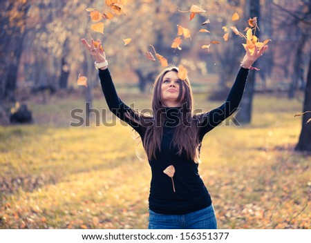 young woman throwing leaves woman in the forest  - stock photo