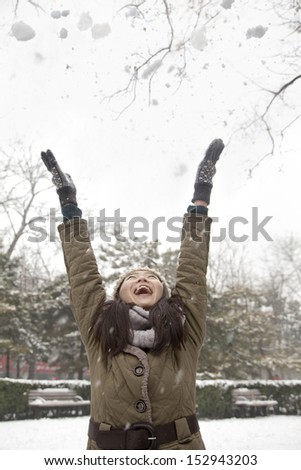 Young woman throwing snow into air in park - stock photo