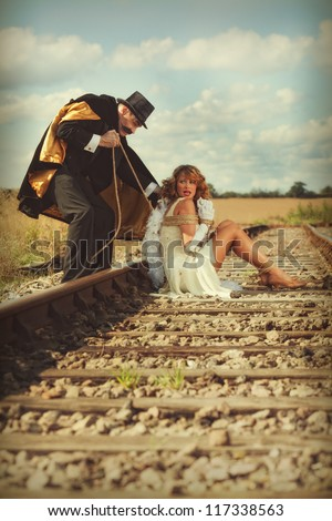Young woman tied to railway track by villain - stock photo