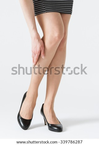 Young woman touching her leg, white background - stock photo