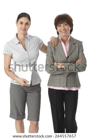 Young woman touching mother's shoulder, holding tablet computer, both smiling. - stock photo