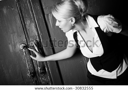 Young woman touching old door. Black and whie. - stock photo