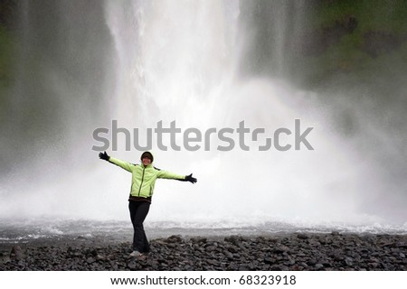 young woman tourist posing in front of Seljalandsfoss waterfall, Iceland - stock photo