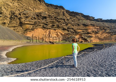 Young woman tourist standing by green water of Lago Verde, El Golfo, Lanzarote, Canary Islands, Spain - stock photo