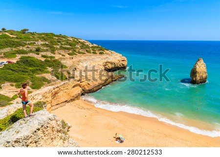 Young woman tourist standing on cliff and looking at beautiful beach near Carvoeiro town, Algarve region, Portugal - stock photo