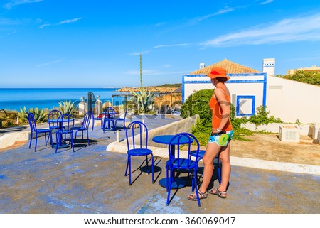 Young woman tourist standing on restaurant terrace with tables near Praia da Rocha beach on coast of Portugal - stock photo