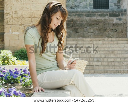 Young woman tourist visiting a monument building and using an mp3 player and headphones while sitting down having a break during a sunny day, outdoors. - stock photo