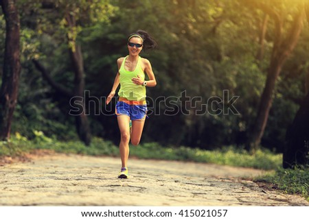young woman trail runner running at forest stone trail - stock photo