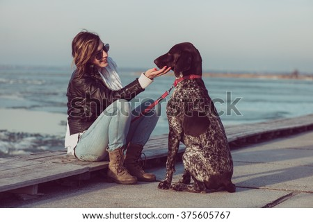 Young woman train her German pointer dog outdoor - stock photo