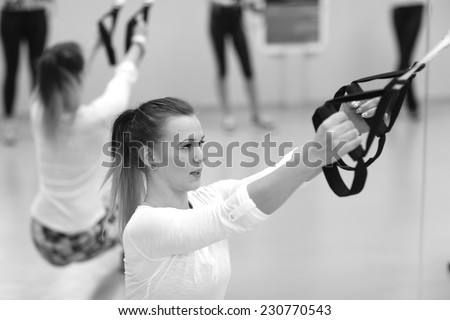 Young woman training with resistance band, monochrome - stock photo