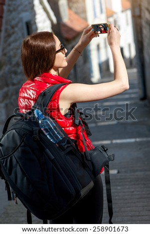 Young woman traveler in red sportswear taking selfie photo with smart phone in old city street in the morning. - stock photo