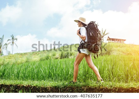 Young woman traveling among rice fields with backpack (intentional sun glare) - stock photo