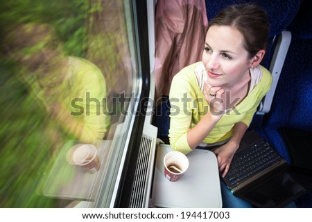 Young woman traveling by train (landscape moving fast behind the window (<--- motin blurred image) - stock photo