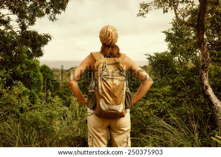 Young woman traveller with backpack in a woods. Hiking at summertime. - stock photo