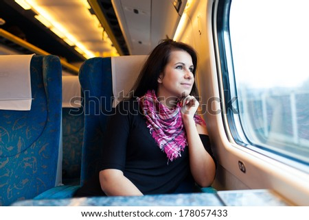 Young woman travelling by train , College student looking out of window - stock photo