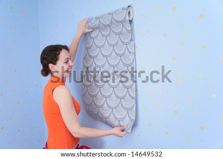 young woman tries on wall-papers to wall - stock photo
