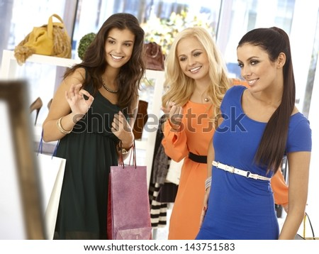 Young woman trying on blue dress at clothes store, friends commenting, all smiling. - stock photo