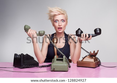 young woman trying to answer the phones but failing - stock photo