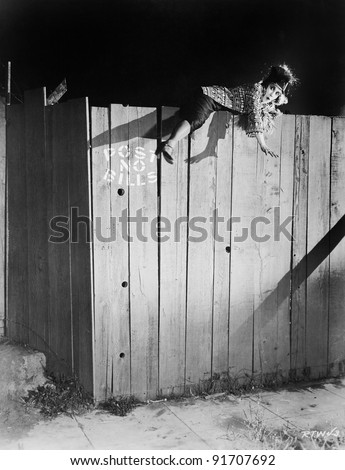Young woman trying to climb over a wooden fence - stock photo