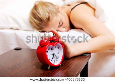 Young woman trying to sleep when alarm clock ringing - stock photo