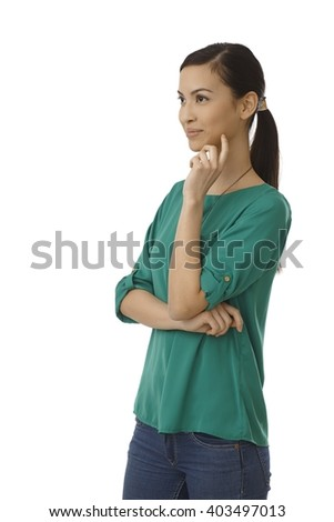Young woman turning right with arms crossed, smiling hand on chin. - stock photo