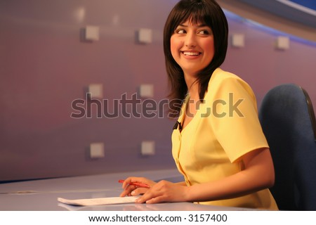 Young woman TV reporter smiling and looking back while preparing for the news presenting - stock photo