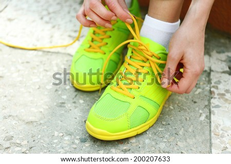 Young woman tying shoelace outside - stock photo