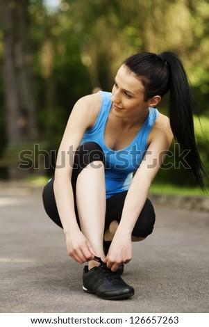 Young woman tying sports shoe - stock photo