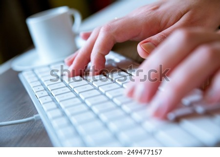 Young woman typing on a white modern computer keyboard while having a coffee on the side. - stock photo