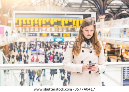 Young woman typing on her smart phone at train station. She is on her mid twenties, alone, looking at the phone while waiting for a train or for a friend. Travel and lifestyle concepts. - stock photo