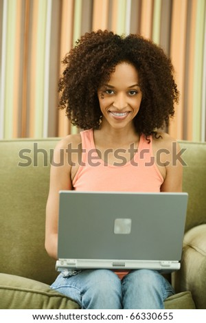 Young woman typing with laptop - stock photo